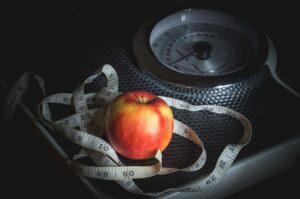 Op deze foto zie je een weegschaal met appel en meetlint