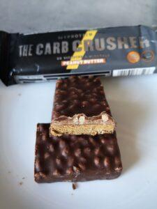Op deze foto zie je de smaak Peanut butter van de THE Carb Crusher eiwitreep