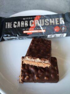 Op deze foto zie je de smaak Strawberry Cheesecake van de THE Carb Crusher eiwitreep