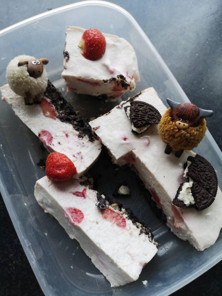 Op deze foto zie je allemaal stukjes Oreo Cheesecake met Aardbeien en Whey
